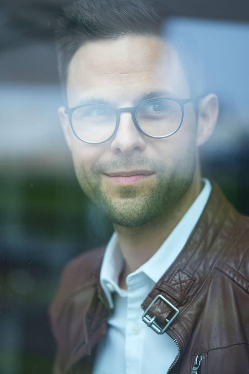 Portrait von Kai Fischer hinter einer Scheibe - Kai Fischer - Moderator - kaifischer.tv